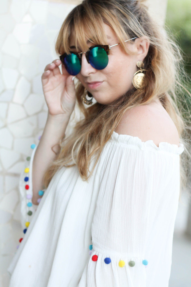 What to wear in Barcelona: pom pom off the shoulder top and major earrings.