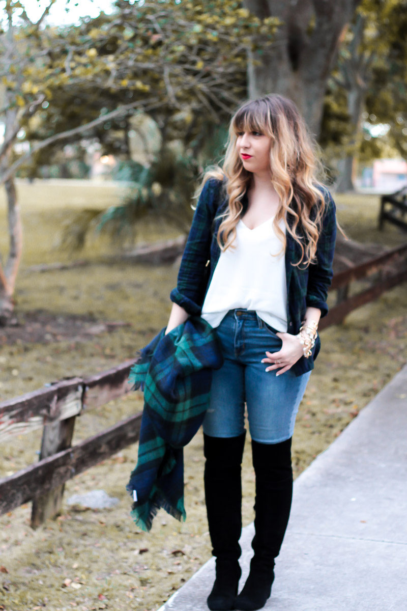 Miami fashion blogger Stephanie Pernas styles a black watch plaid blanket scarf and top with jeans and over the knee boots for a cute casual fall outfit idea