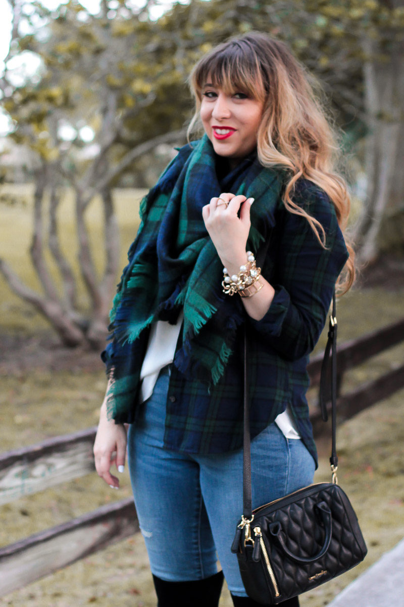 Miami fashion blogger Stephanie Pernas styles a black watch plaid blanket scarf with a coordinating button down for a chic and easy casual holiday outfit