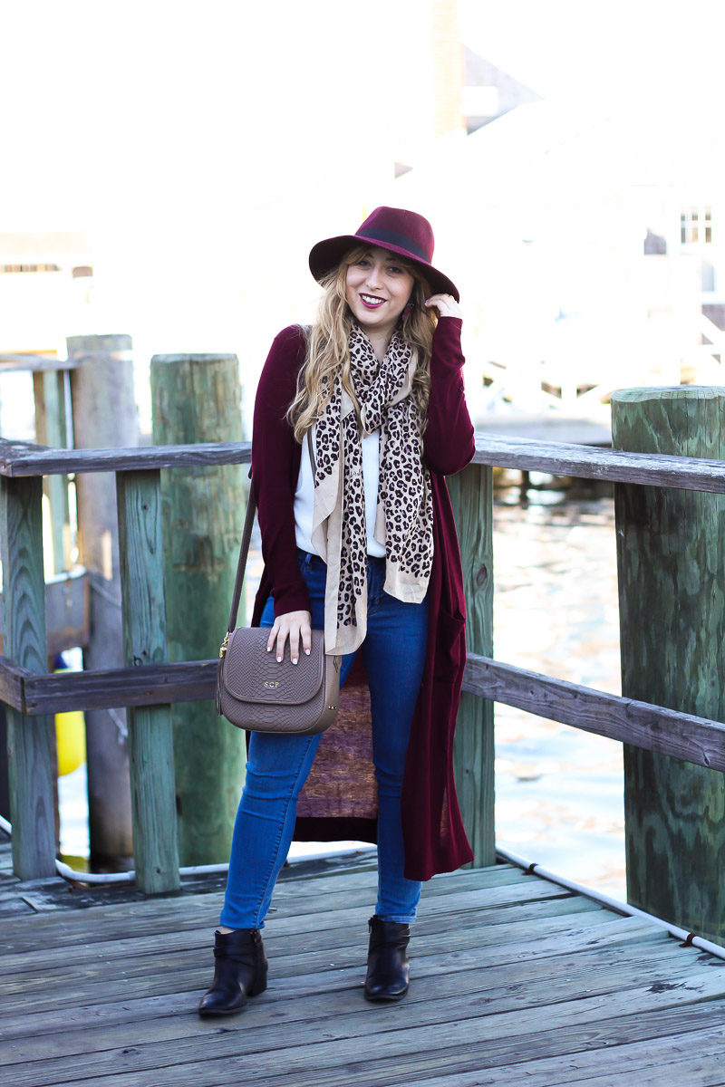 Miami fashion blogger Stephanie Pernas wearing a wine colored fedora with a long duster cardigan, jeans, and ankle boots for a chic fall look