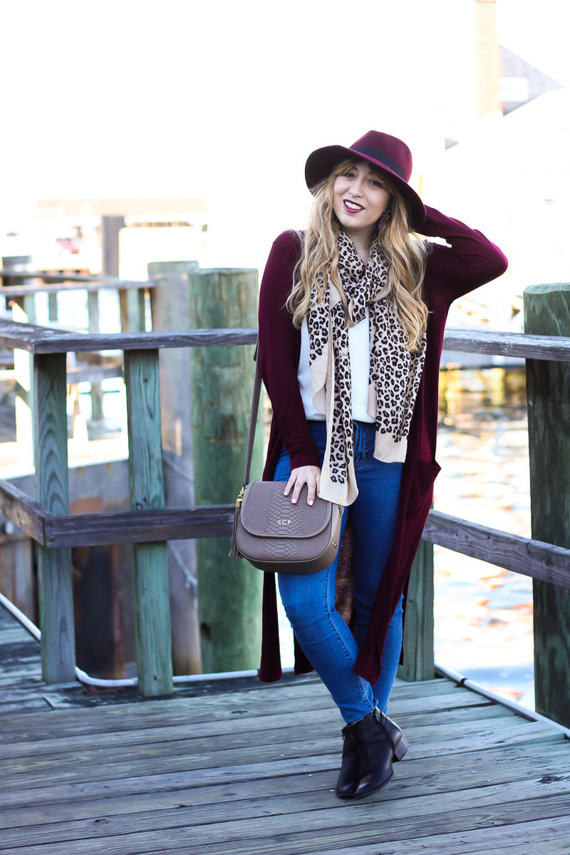 Miami fashion blogger styles a long wine colored cardigan with jeans, booties and a leopard scarf for a cool fall outfit