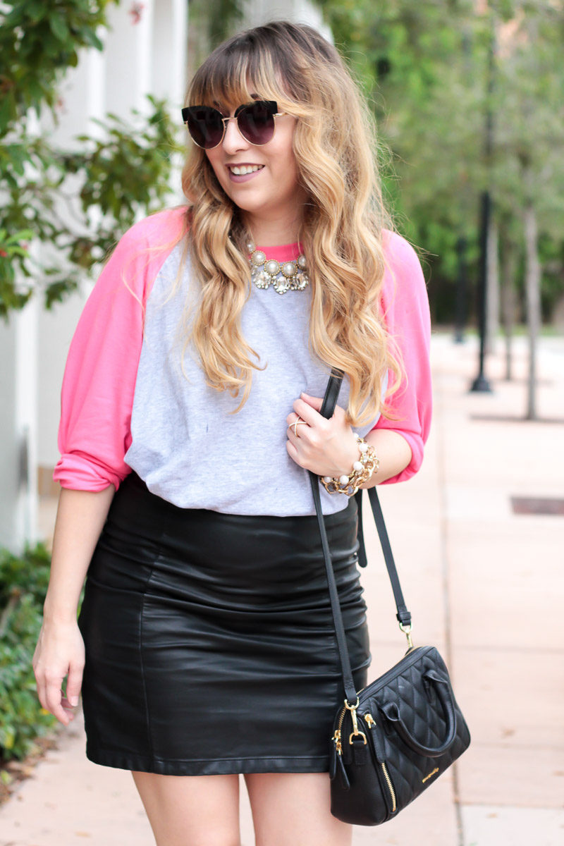 Miami fashion blogger Stephanie Pernas dresses up a baseball tee and leather skirt outfit with a stack of statement necklaces
