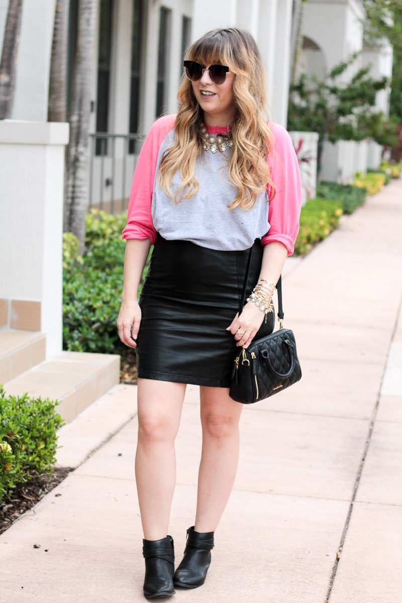 Miami fashion blogger Stephanie Pernas styling a cute baseball tee with a leather mini skirt and booties