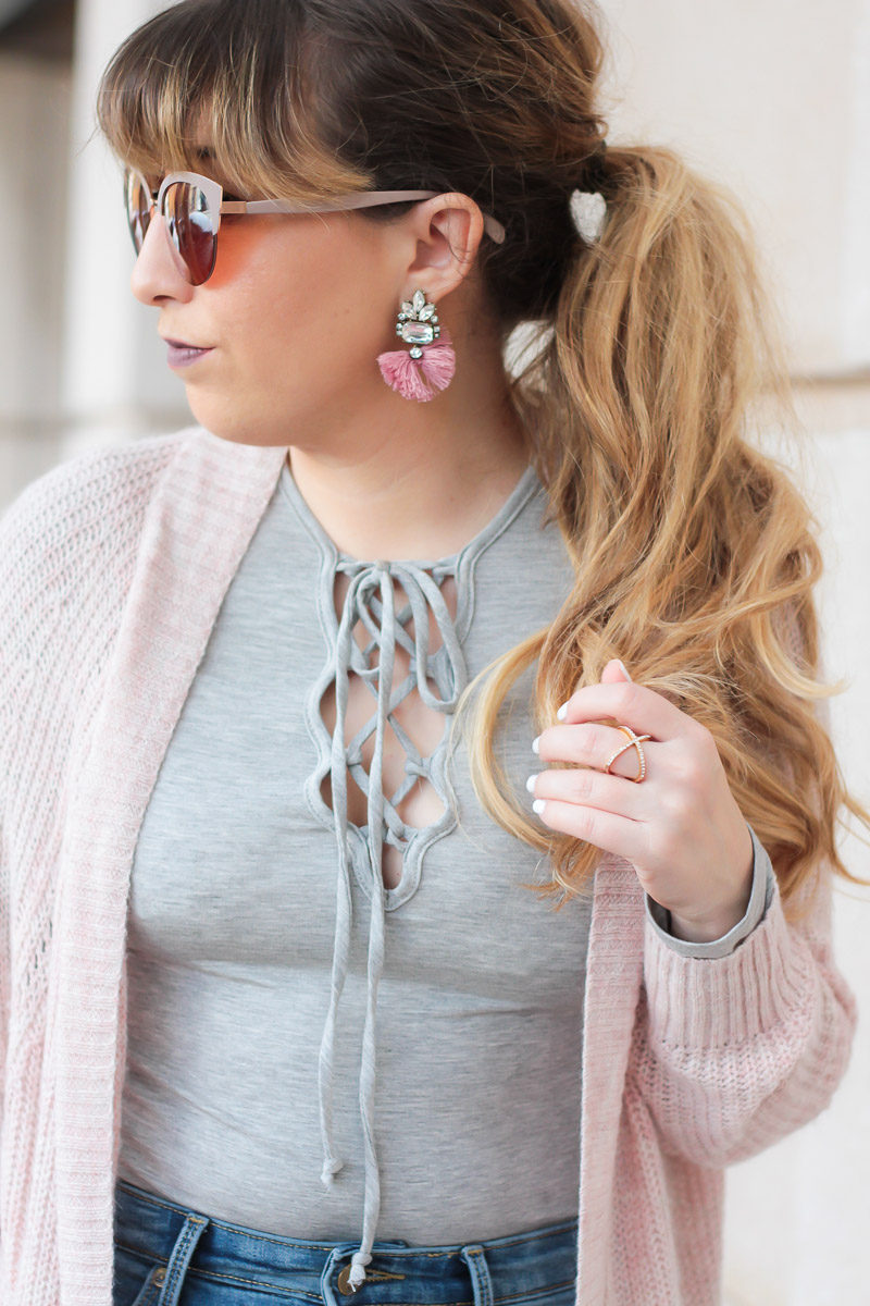 Miami fashion blogger Stephanie Pernas of A Sparkle Factor pairs a gray lace up tee and cozy pink cardigan with pink Baublebar Flamenco Drops earrings