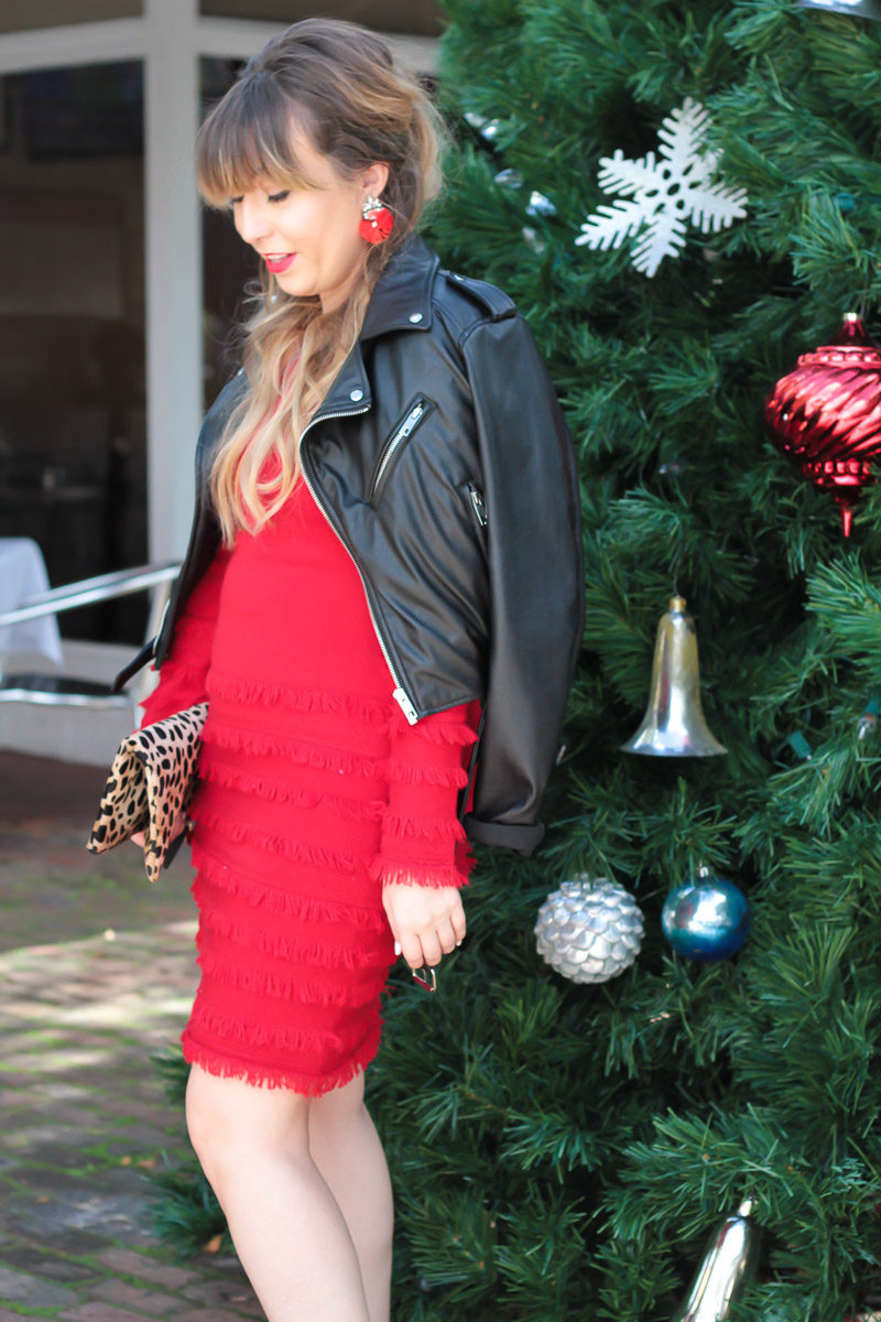 Fashion blogger wearing a red dress and red earrings for a chic holiday outfit idea