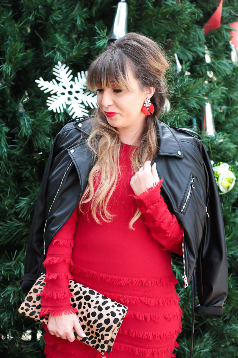 Fashion blogger Stephanie Pernas styles a leather jacket over a red fringe sweaterdress for a festive holiday outfit idea