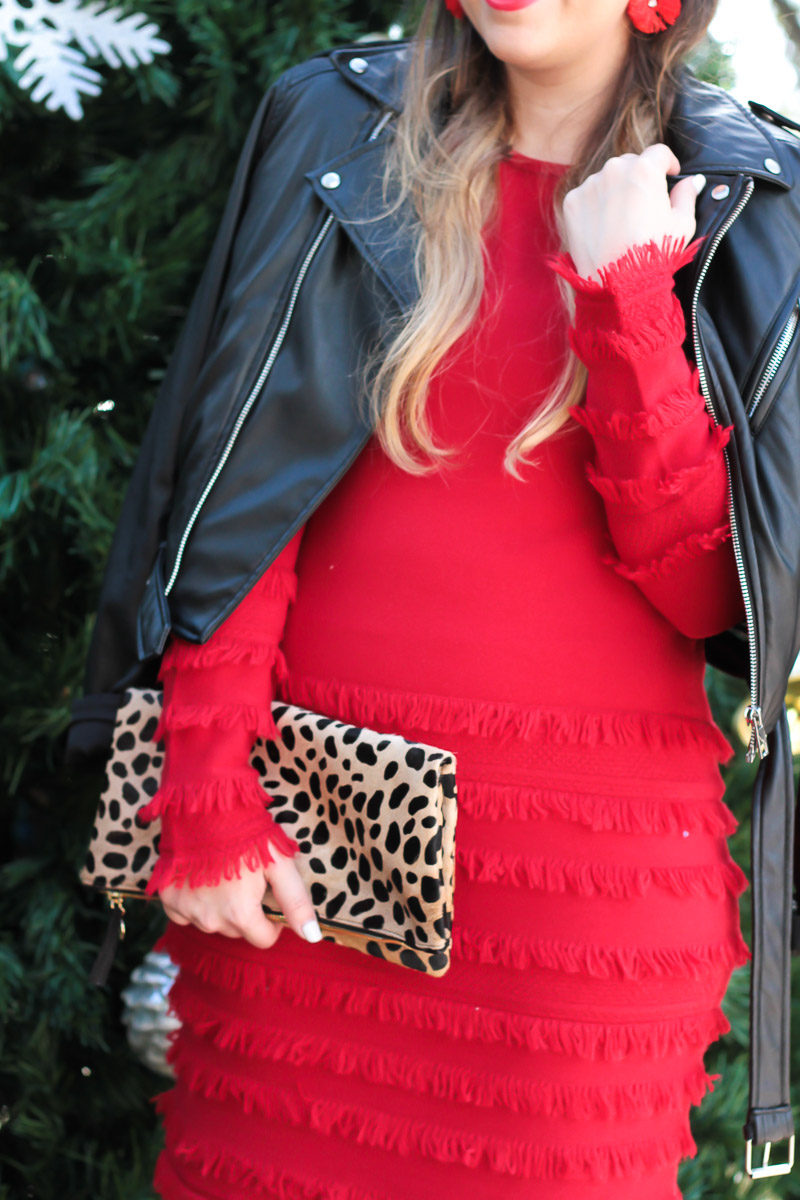 Miami fashion blogger Stephanie Pernas styling a red fringe sweater dress with a leopard clutch for a pretty holiday outfit idea