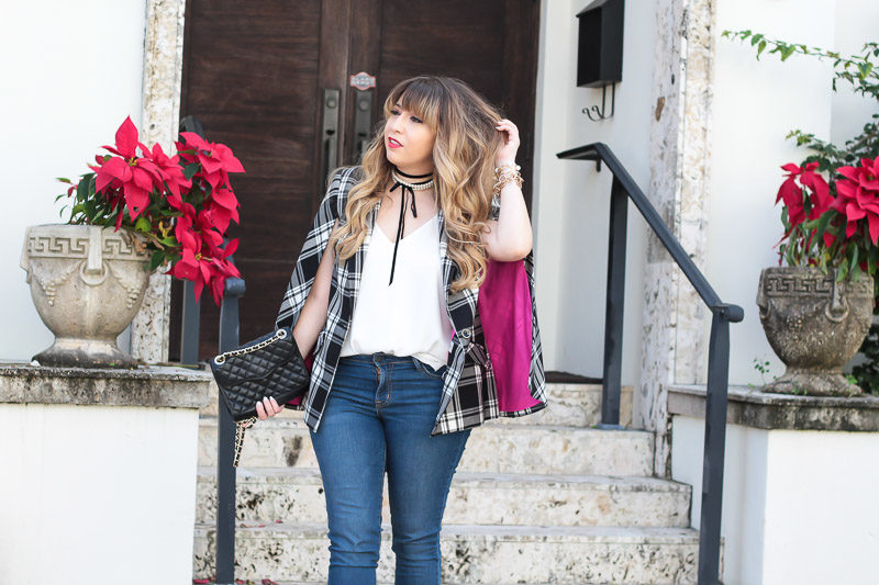 Miami fashion blogger Stephanie Pernas styles a plaid cape blazer and jeans for a casual holiday outfit idea