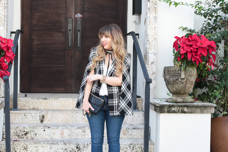 Miami fashion blogger Stephanie Pernas styles a plaid cape blazer with a pearl choker and jeans for a casual polished look