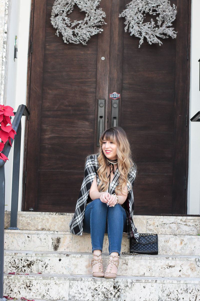Fashion blogger Stephanie Pernas wearing a plaid blazer and jeans for a casual Christmas outfit idea