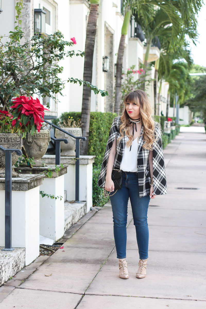 Miami fashion blogger Stephanie Pernas styles a Trina Turk plaid cape blazer with jeans for a classic casual look.