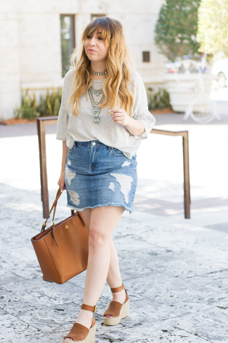 Miami fashion blogger Stephanie Pernas wearing a casual gray ruffle sleeve tshirt outfit with jean skirt and wedges