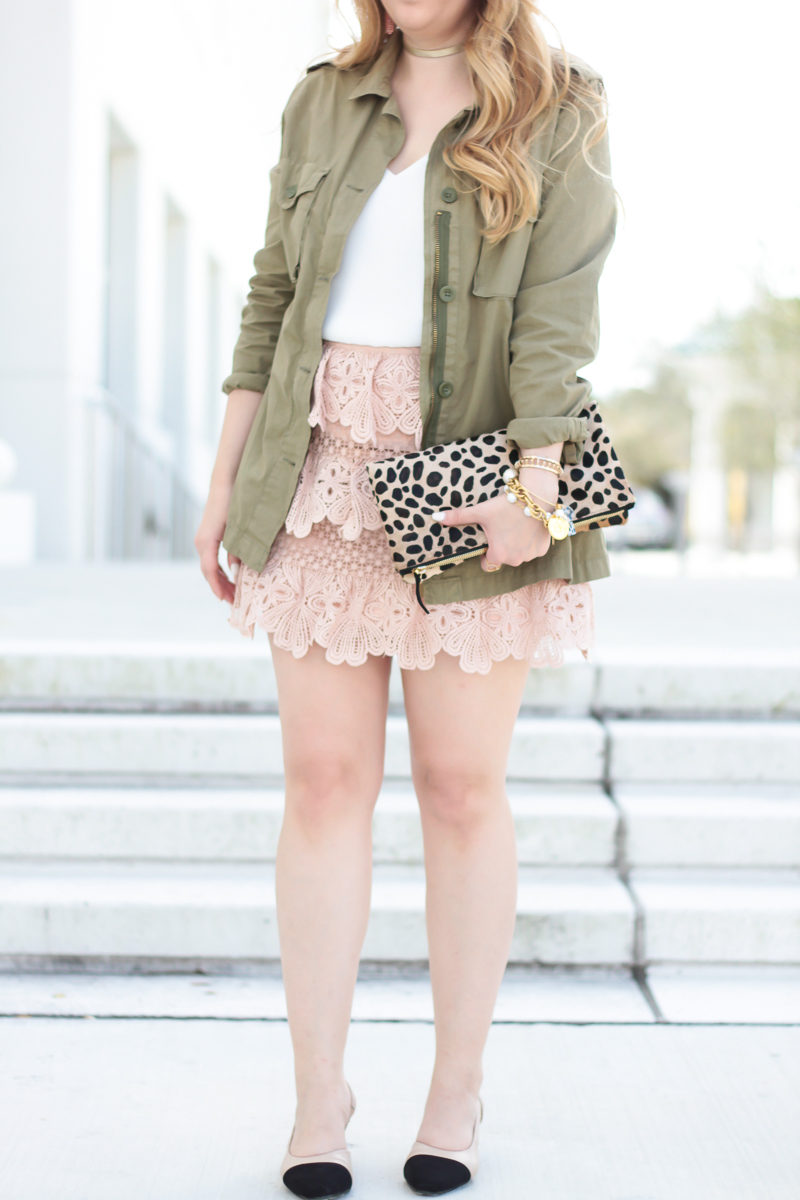 Fashion blogger Stephanie Pernas styles an olive utility jacket with a blush lace skirt for a girly spring outfit idea