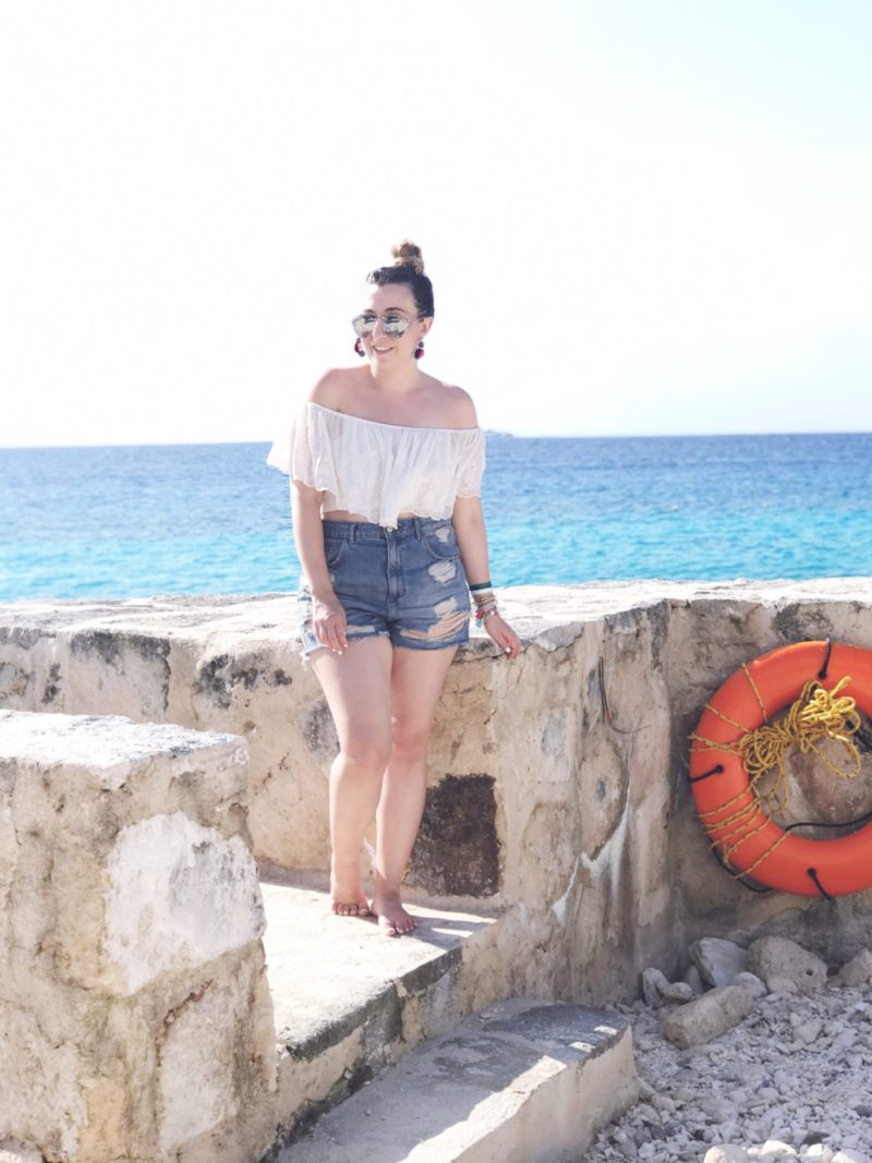 Miami fashion blogger Stephanie Pernas wearing an off the shoulder crop top and jean shorts outfit