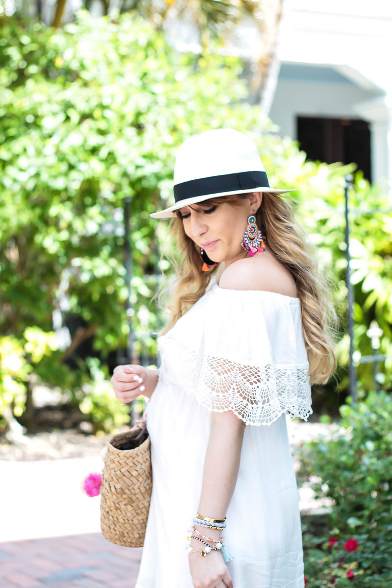 Miami fashion blogger Stephanie Pernas styles a white off the shoulder dress with a panama hat and statement earrings