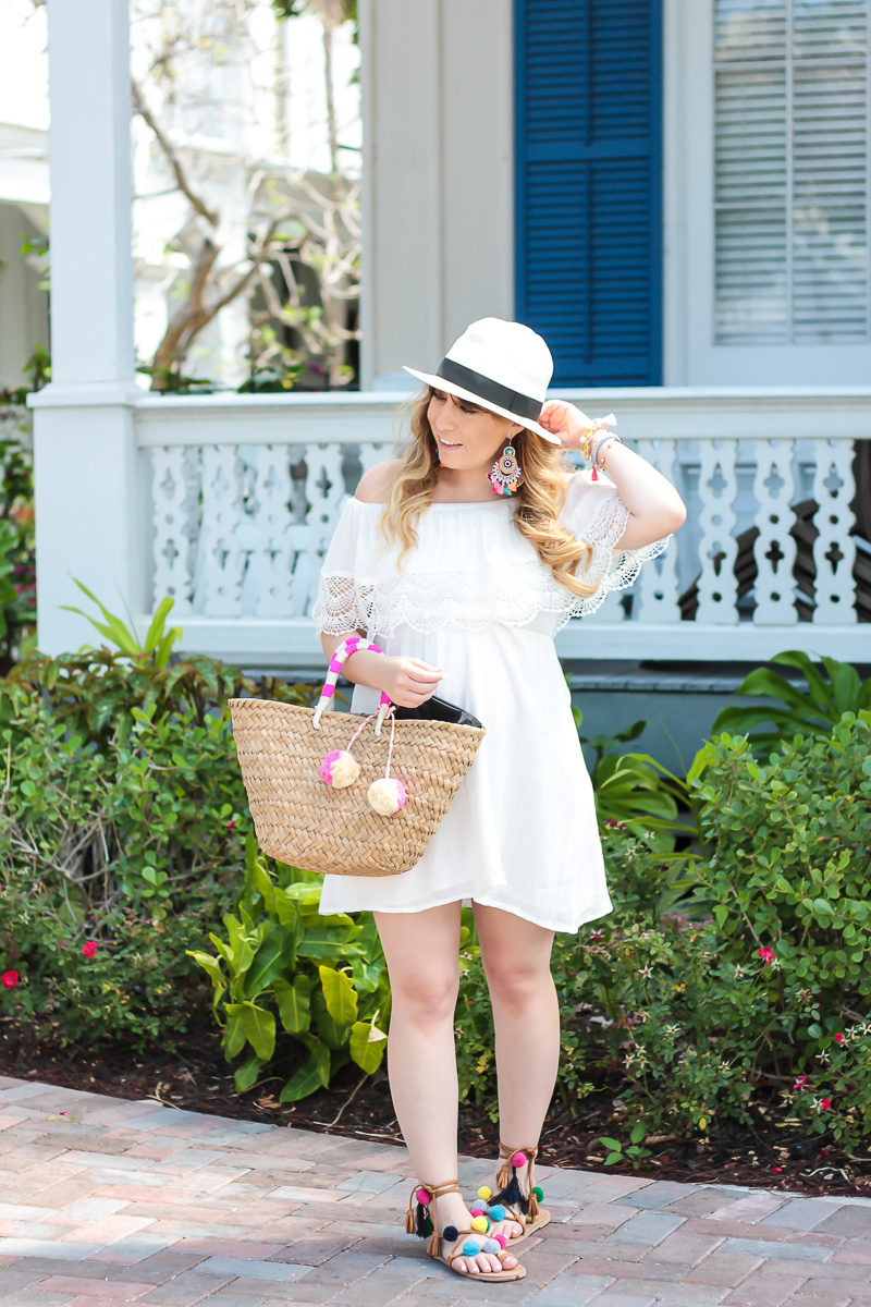 Miami fashion blogger Stephanie Pernas wearing a white ruffle off the shoulder dress and pom pom sandals