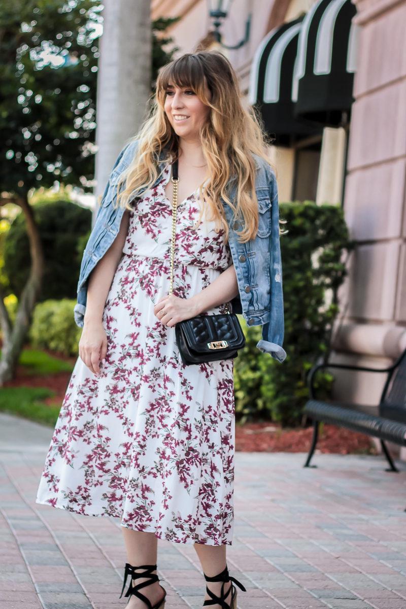 Miami fashion blogger Stephanie Pernas drapes a jean jacket over a floral midi dress