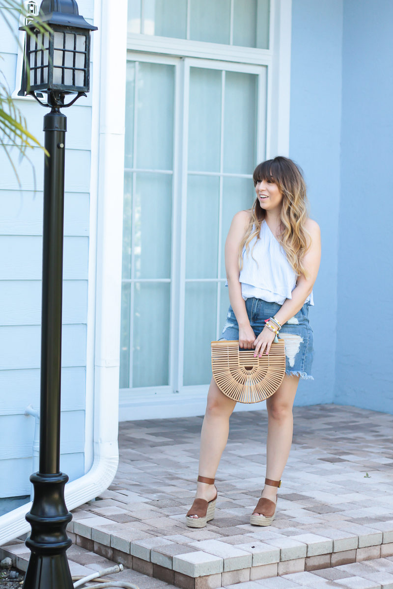 Fashion blogger Stephanie Pernas wearing a blue and white stripe top and jean skirt.