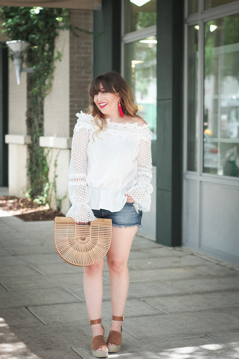 Miami fashion blogger Stephanie Pernas wearing a white lace top and jean shorts for summer