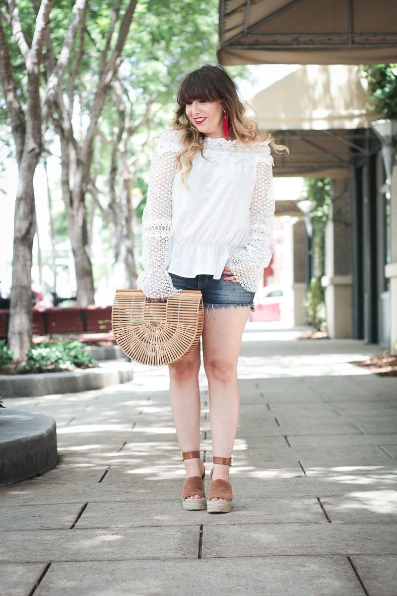 Miami fashion blogger Stephanie Pernas wearing a white lace off the shoulder top and jean shorts