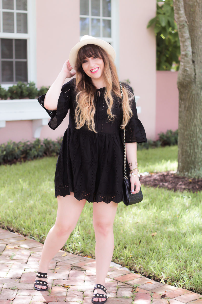 Fashion blogger Stephanie Pernas wearing a black eyelet mini dress and panama hat for summer