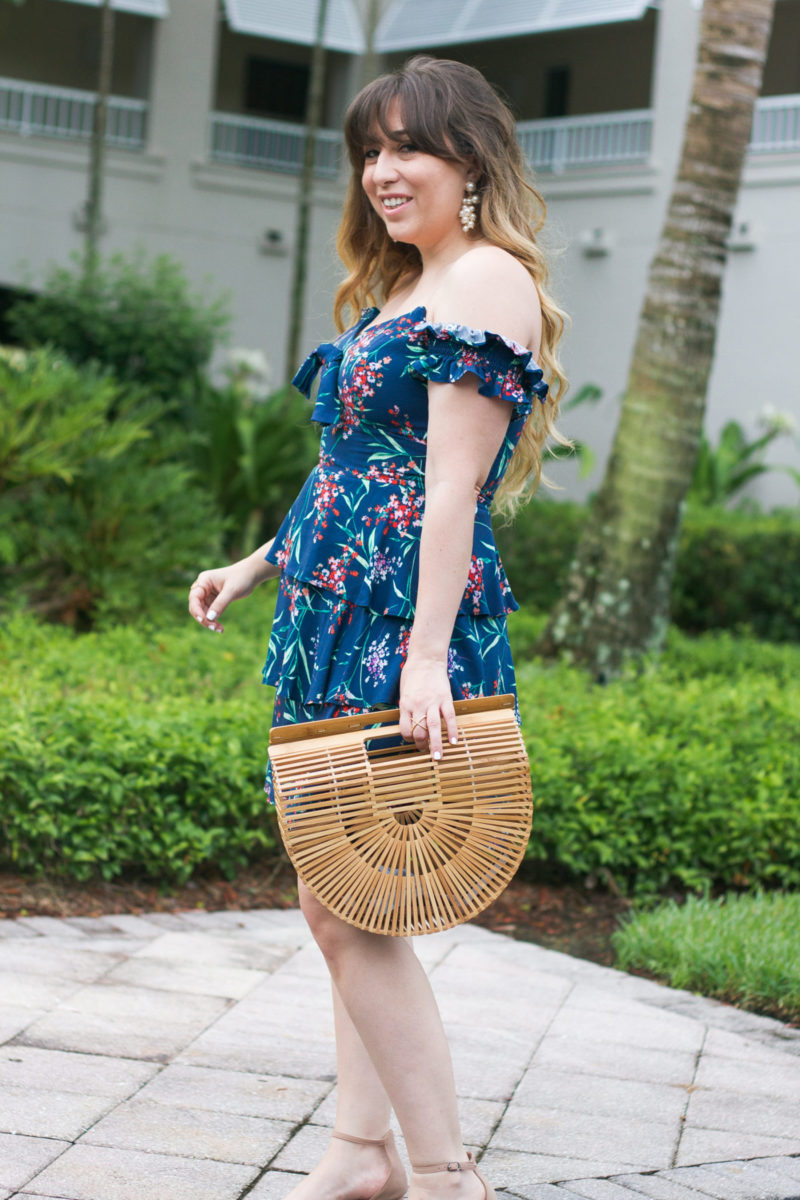 Fashion blogger Stephanie Pernas wearing a floral dress and bamboo bag